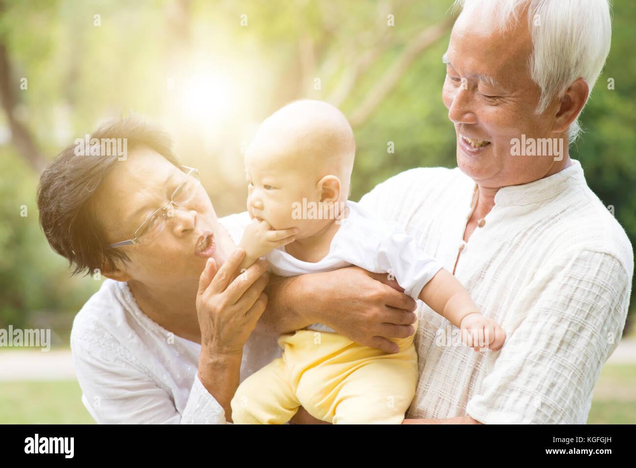 Les grands-parents s'occuper de ses petits-enfants en extérieur parc. asian family, concept d'assurance-vie. Banque D'Images