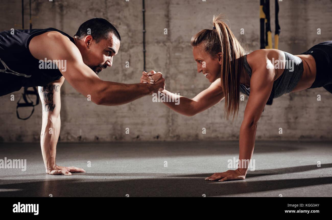 Jeune couple musculaire exercice de force de faire monter à la croix d'entraînement. Photo Stock