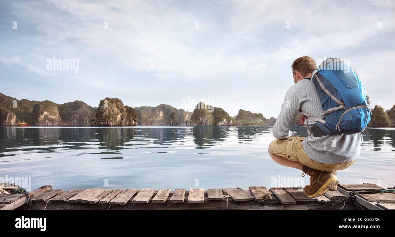 Traveler accroupi sur une jetée Photo Stock
