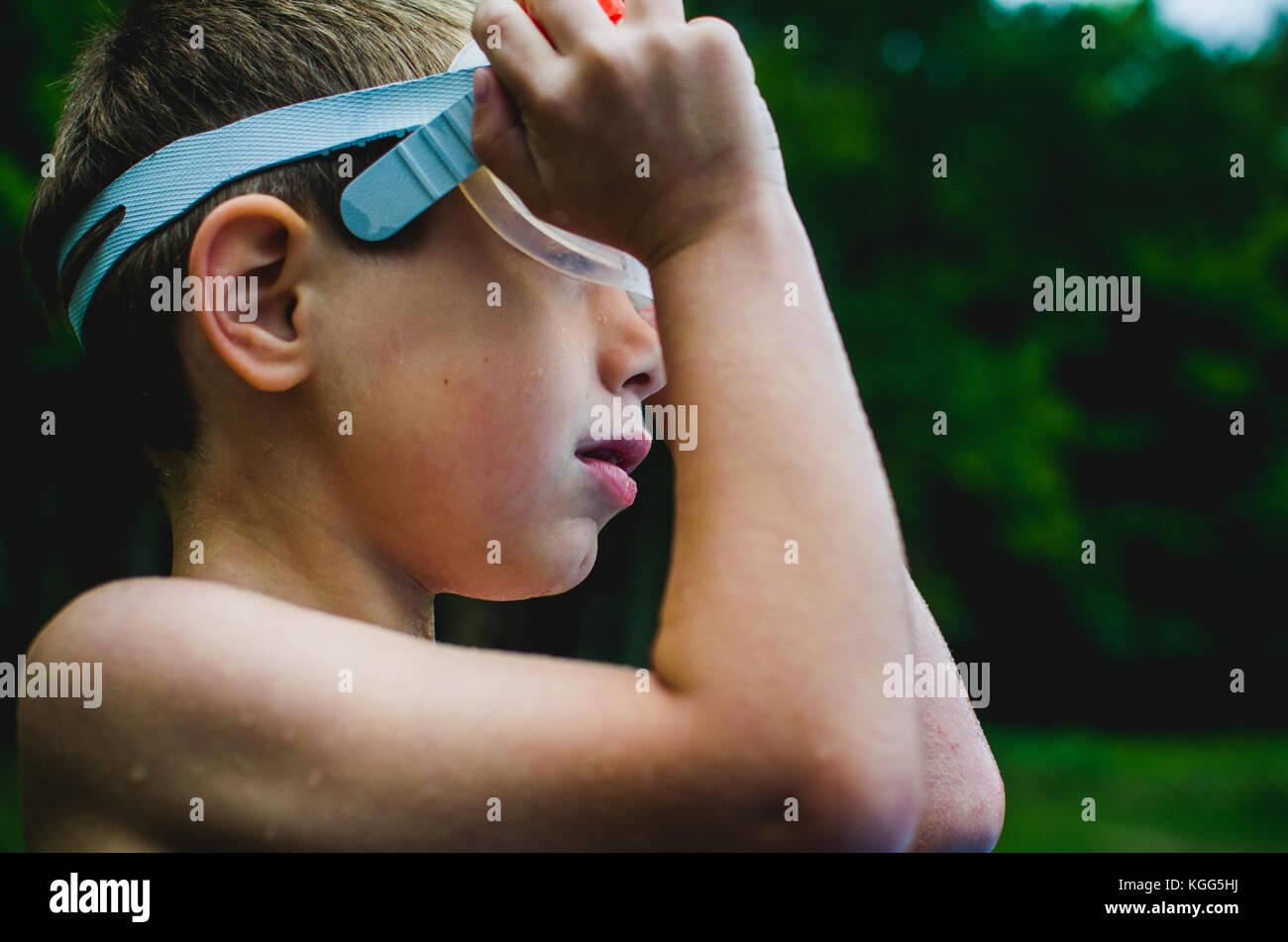 Un jeune garçon ajuste ses lunettes de natation Photo Stock