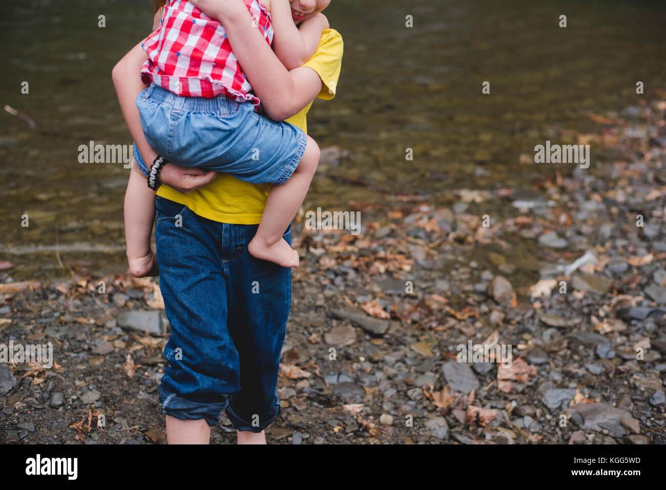 Un garçon porte un enfant dans ses bras Photo Stock