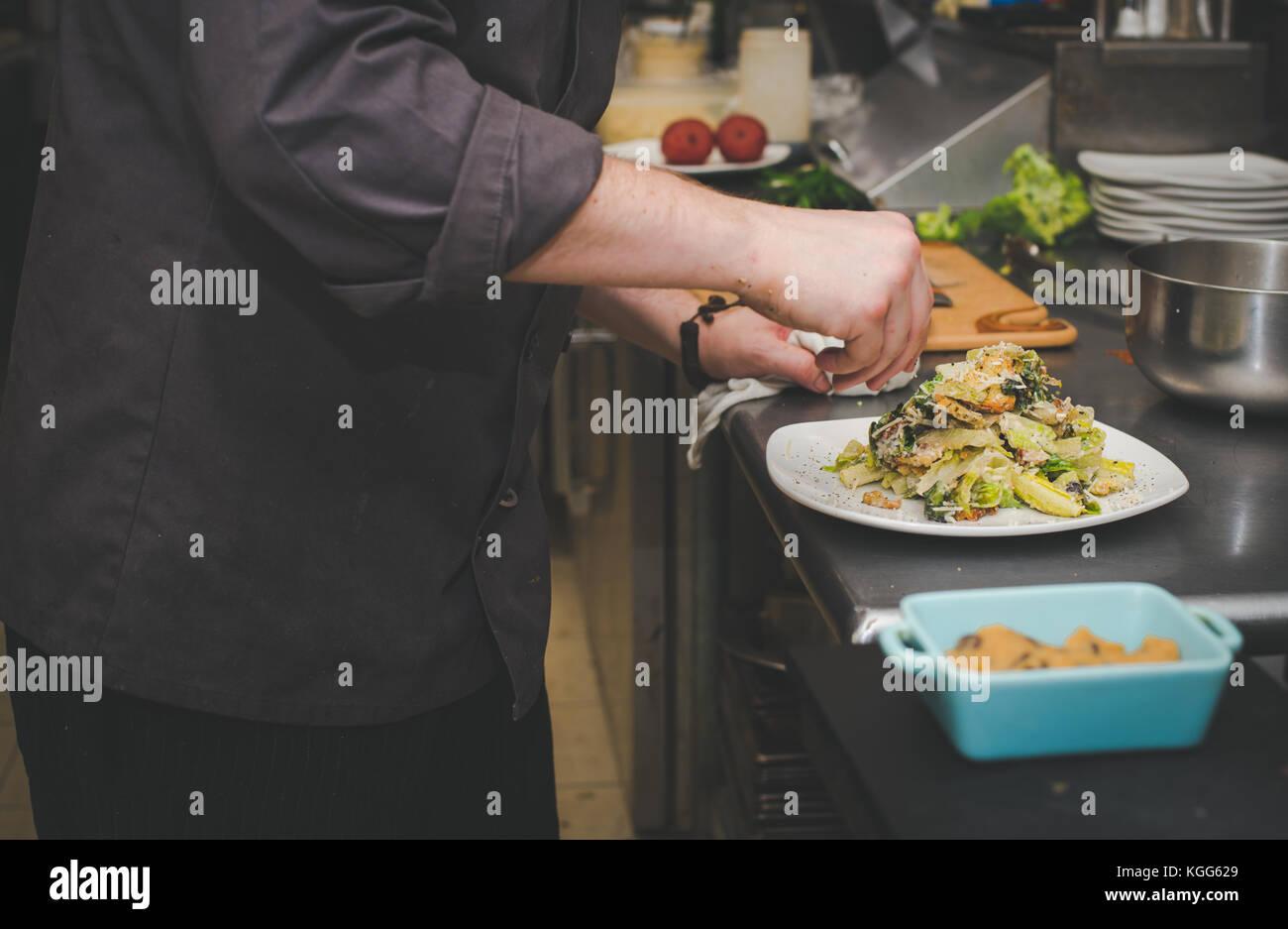 Un chef prépare la nourriture dans la cuisine d'un restaurant Photo Stock