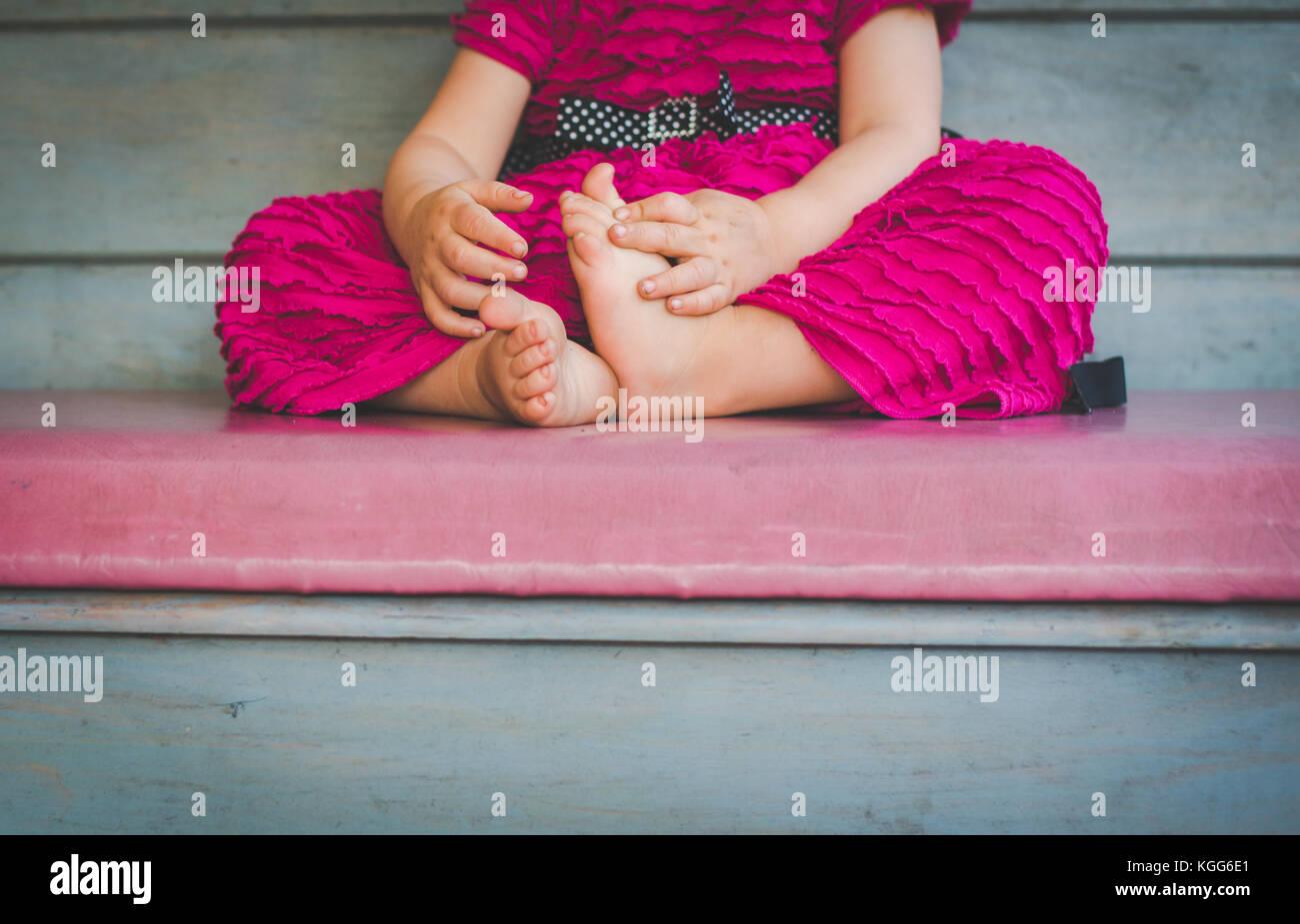 2 à 3 ans, assis sur un banc avec ses pieds nus visibles. Photo Stock