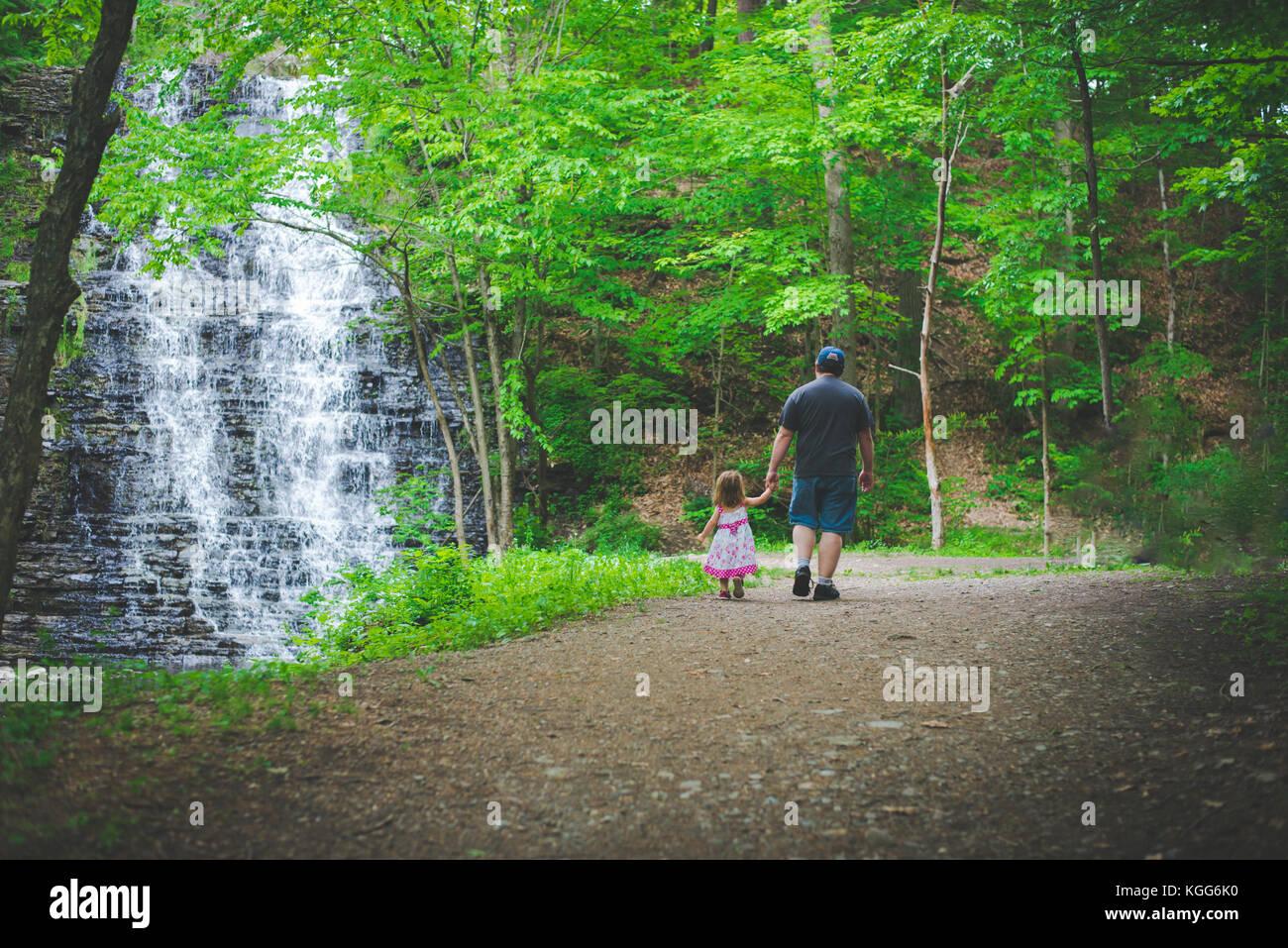 Un enfant marche main dans la main avec son père le long d'un chemin en bois Photo Stock