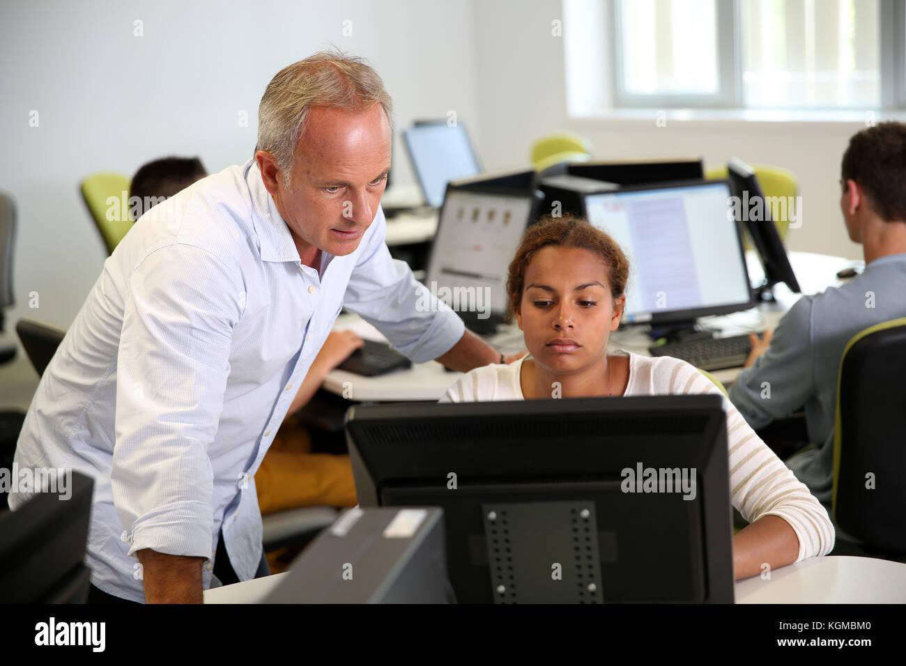 Avec l'enseignant étudiant travaillant sur ordinateur de bureau Photo Stock