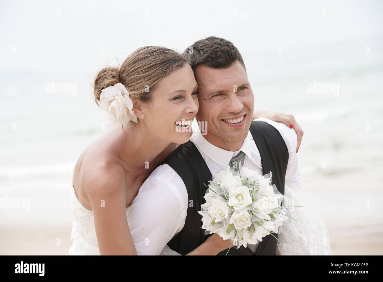 Groom donner piggyback ride à bride sur la plage Photo Stock