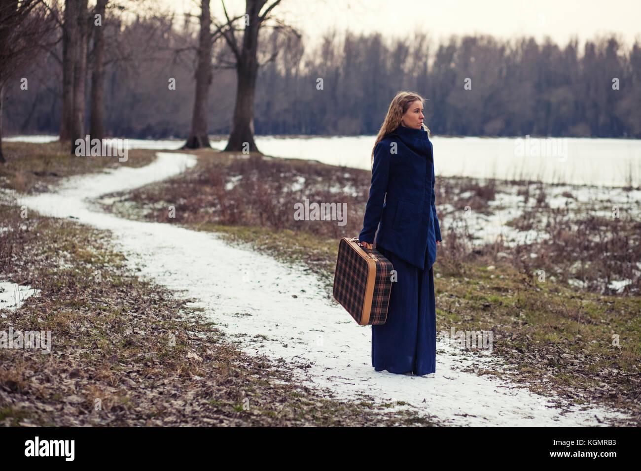Femme marche en forêt avec vieille valise Photo Stock