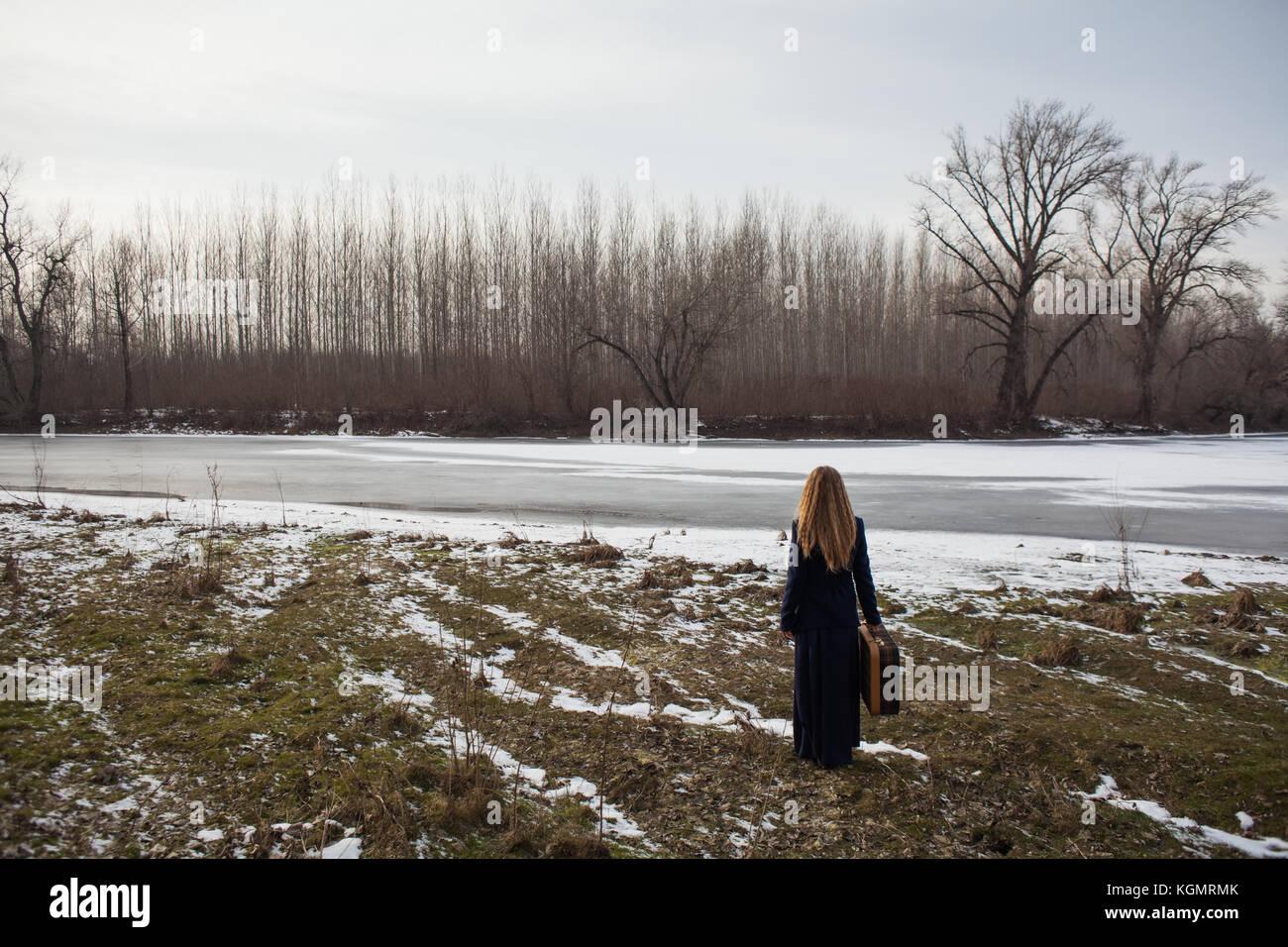 Femme debout près de rivière avec vieille valise et à la recherche d'un moyen d'aller Photo Stock