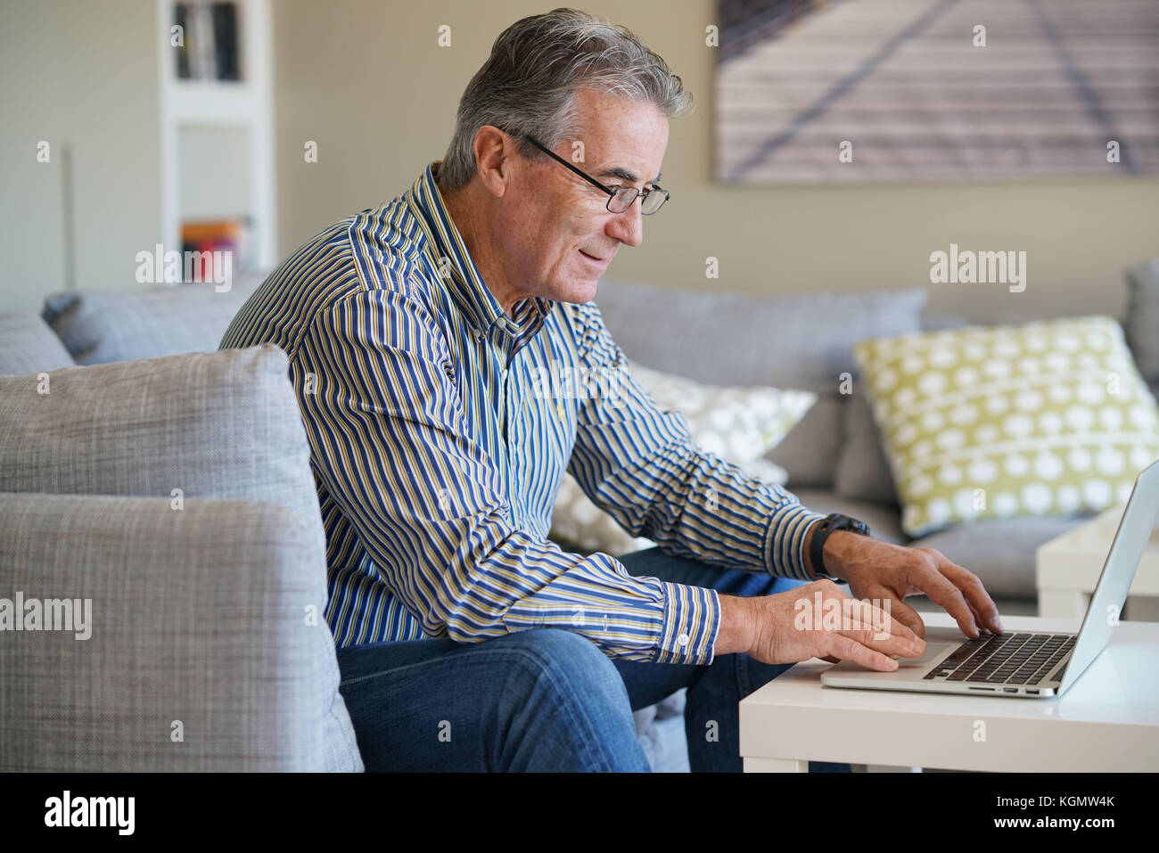 Senior man in living-room using laptop computer Photo Stock