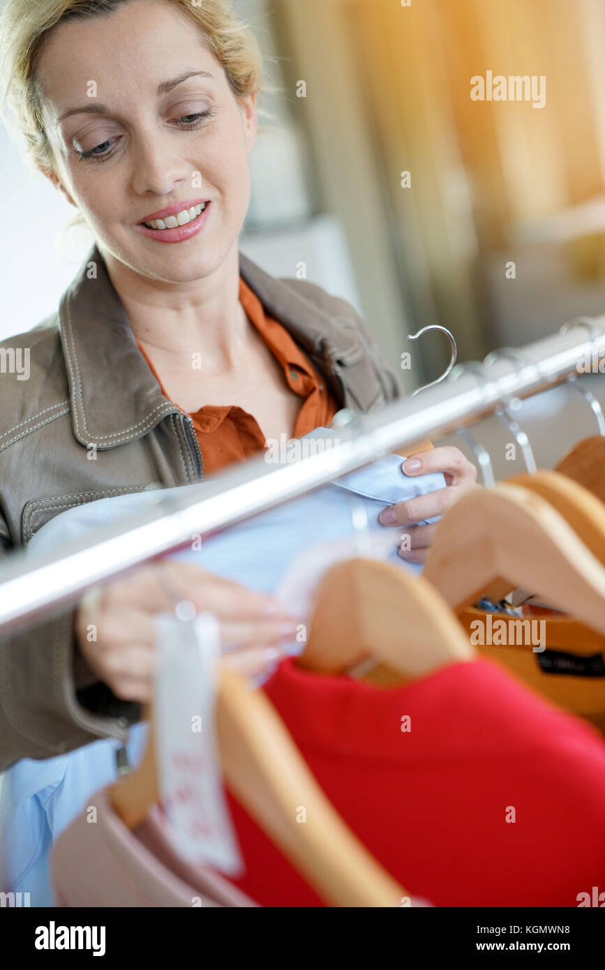 Middle-aged woman shopping in clothing store au cours de saison de ventes Photo Stock