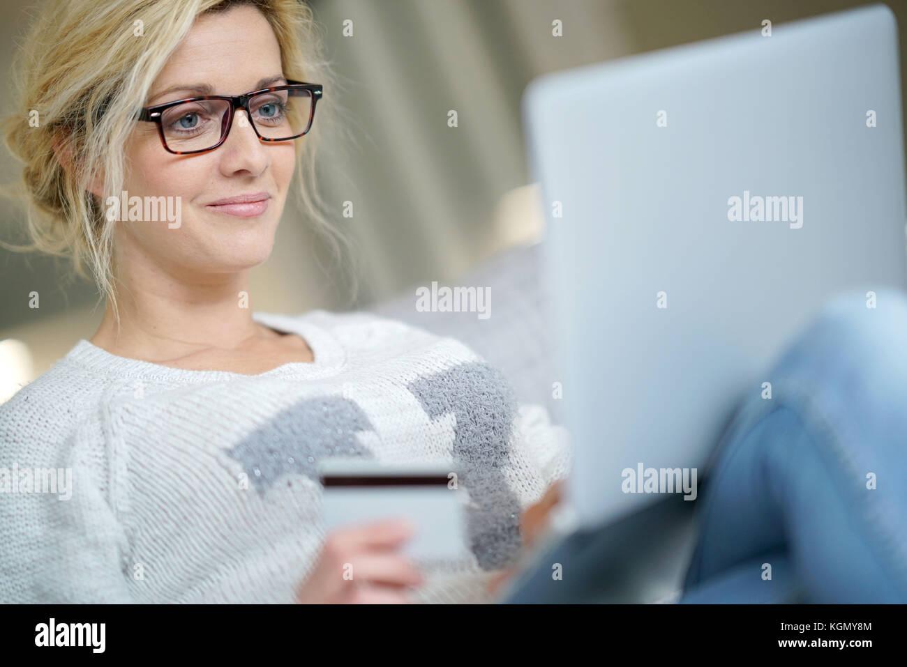 Femme d'âge moyen à la maison l'achat sur internet avec carte de crédit Banque D'Images
