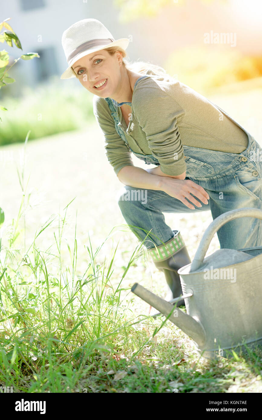 Blonde woman with hat le jardinage sur sunny day Photo Stock