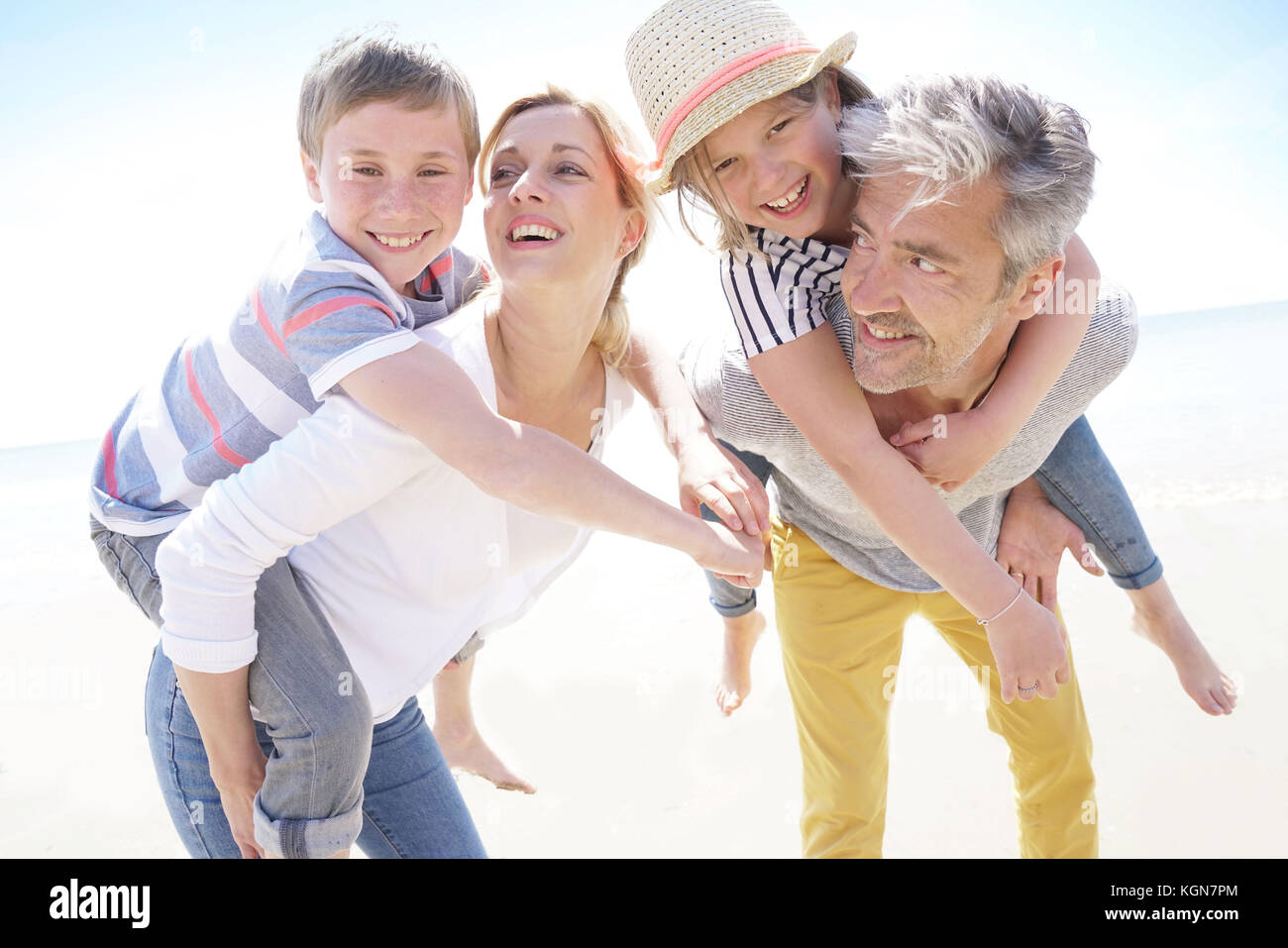 Les parents qui piggyback ride pour enfants à la plage Photo Stock