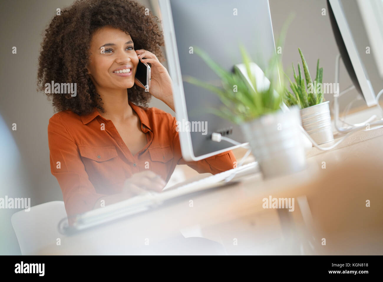 Cheerful businesswoman talking on phone in office Photo Stock