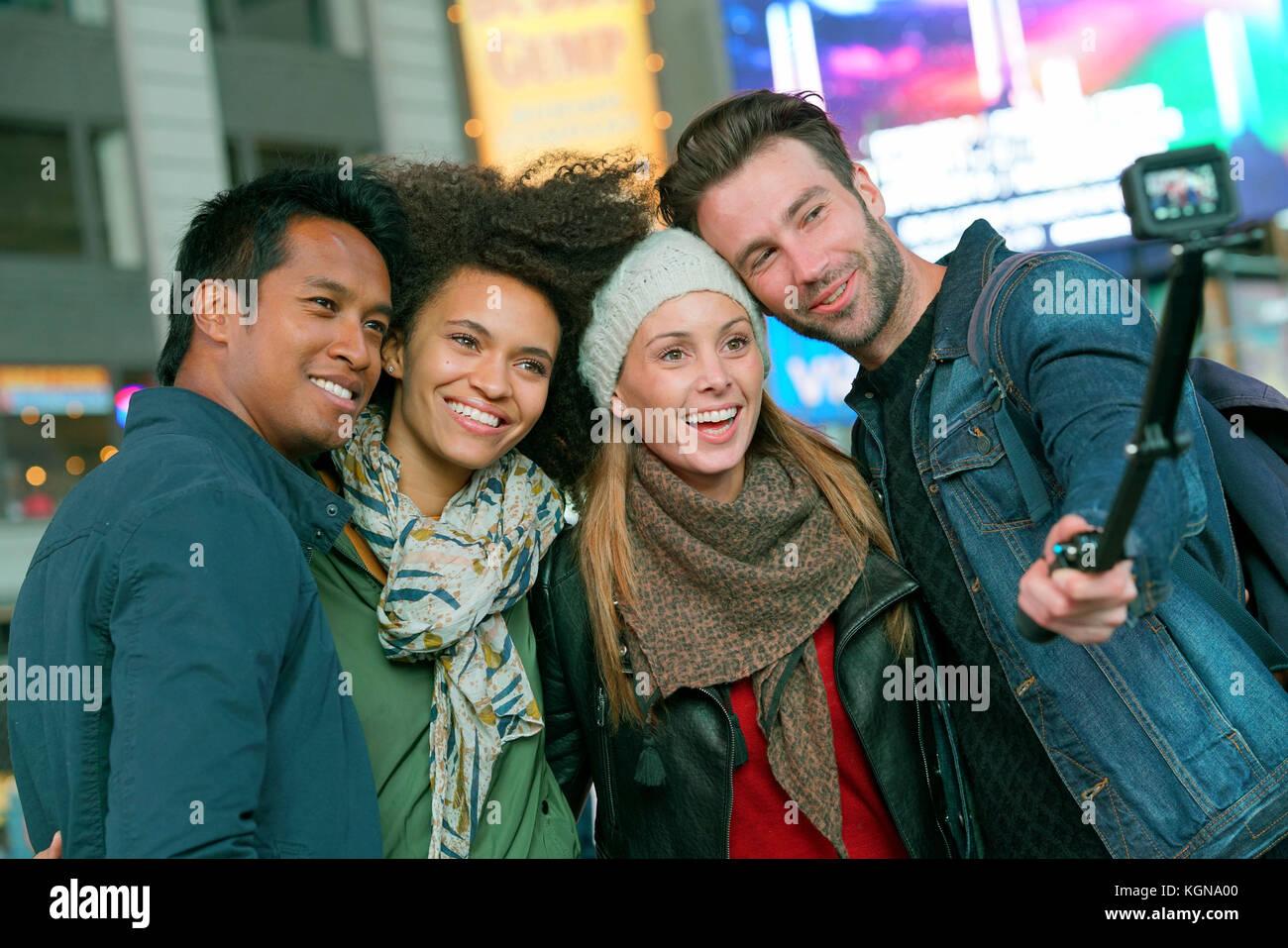 Amis à Times square en tenant photo selfies Photo Stock