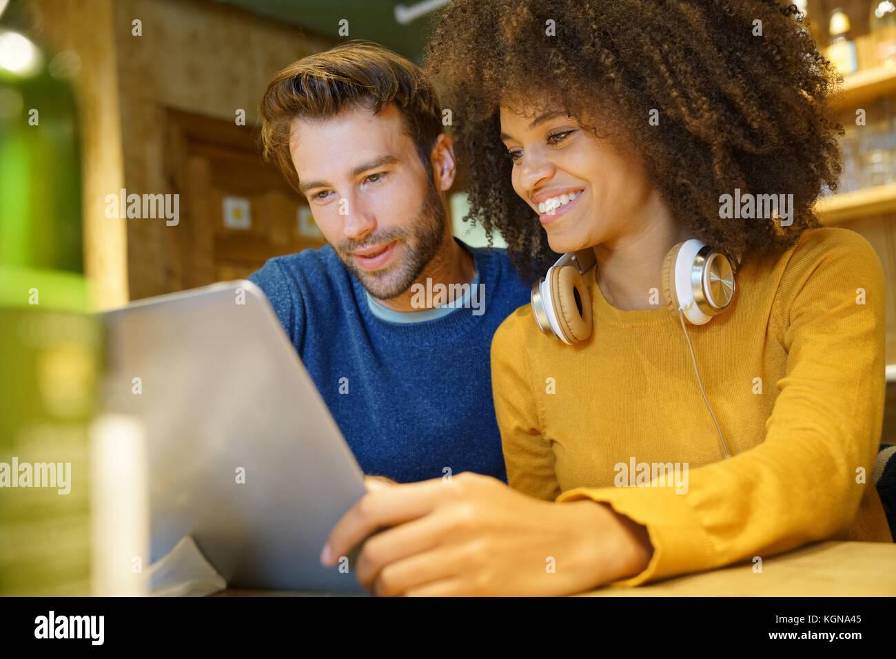 Couple in restaurant branché sur Internet avec ordinateur portable Photo Stock