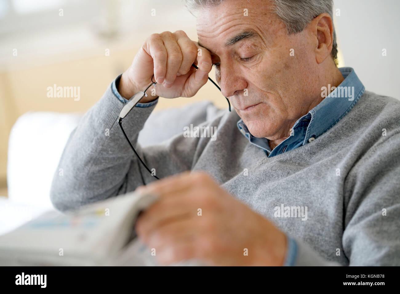 Having a headache senior man reading newspaper Banque D'Images