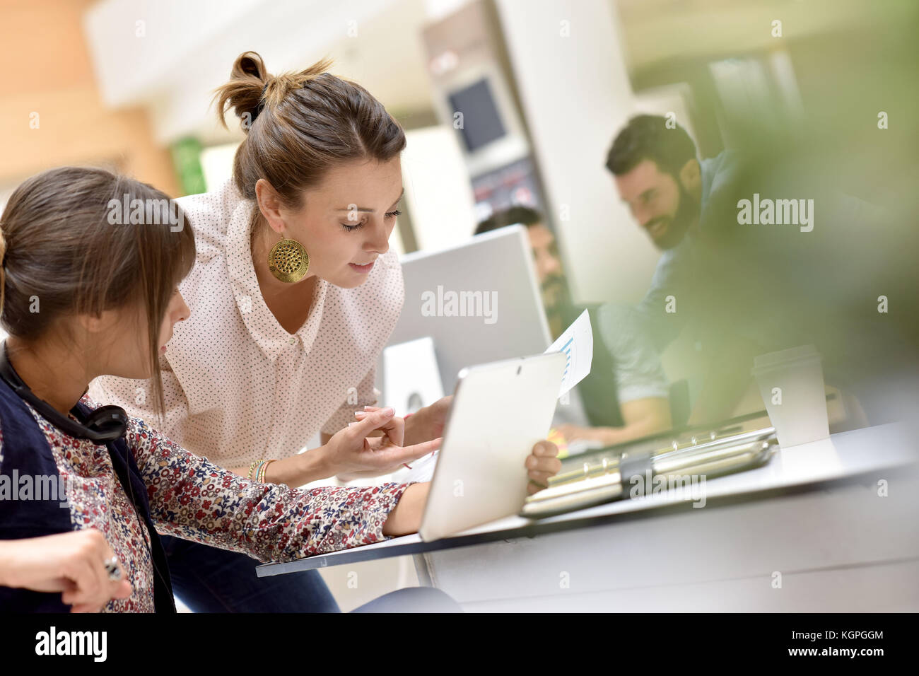 Les jeunes femmes en travail de bureau sur tablette numérique Banque D'Images