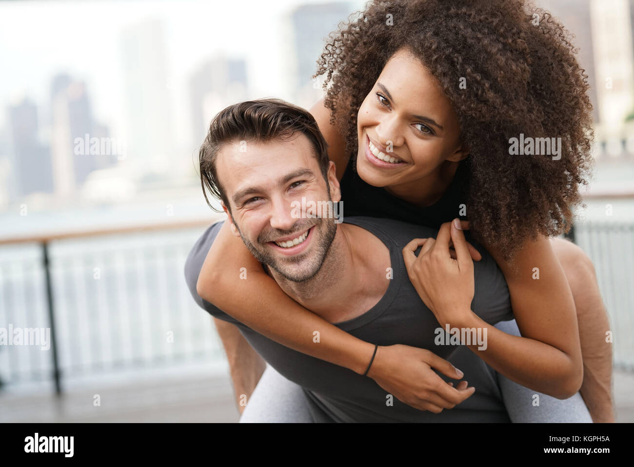 Man giving piggyback ride to girlfriend Photo Stock