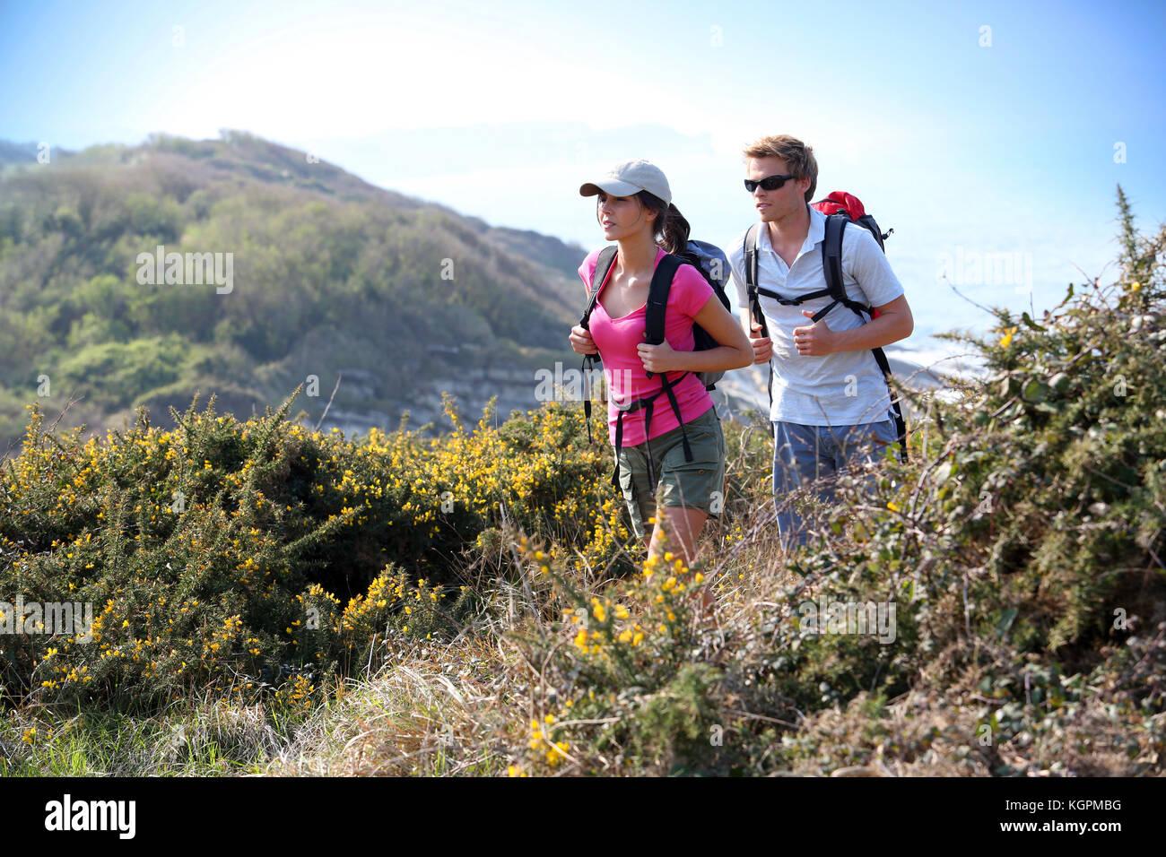 Couple de randonneurs dans le champ pays par l'océan Photo Stock
