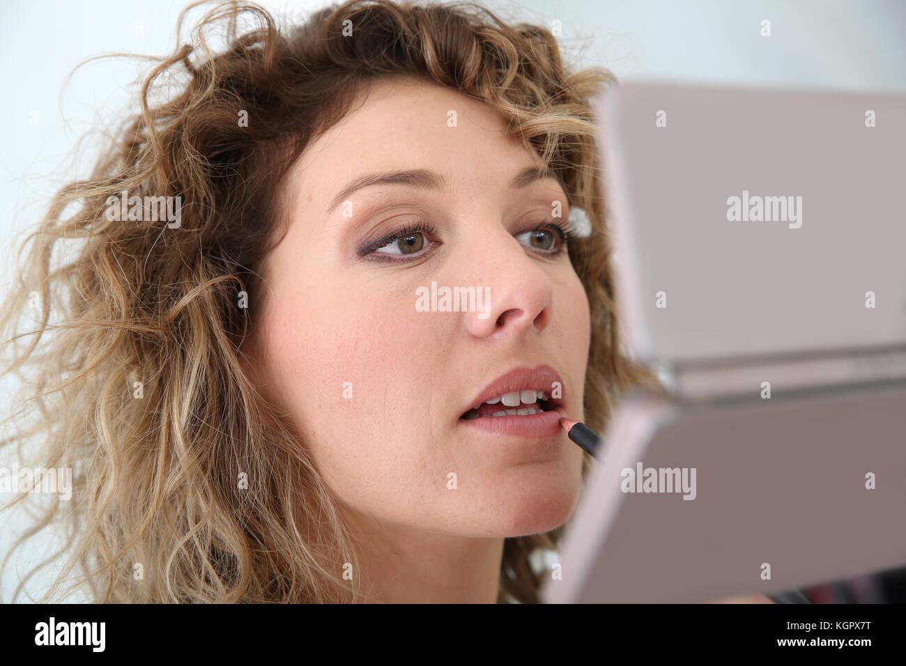 Woman applying makeup sur ses lèvres Photo Stock