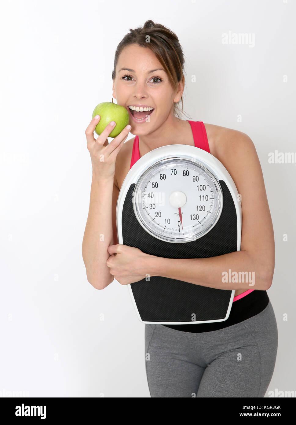 Cheerful girl en tenue de remise en forme et l'échelle holding green apple Photo Stock