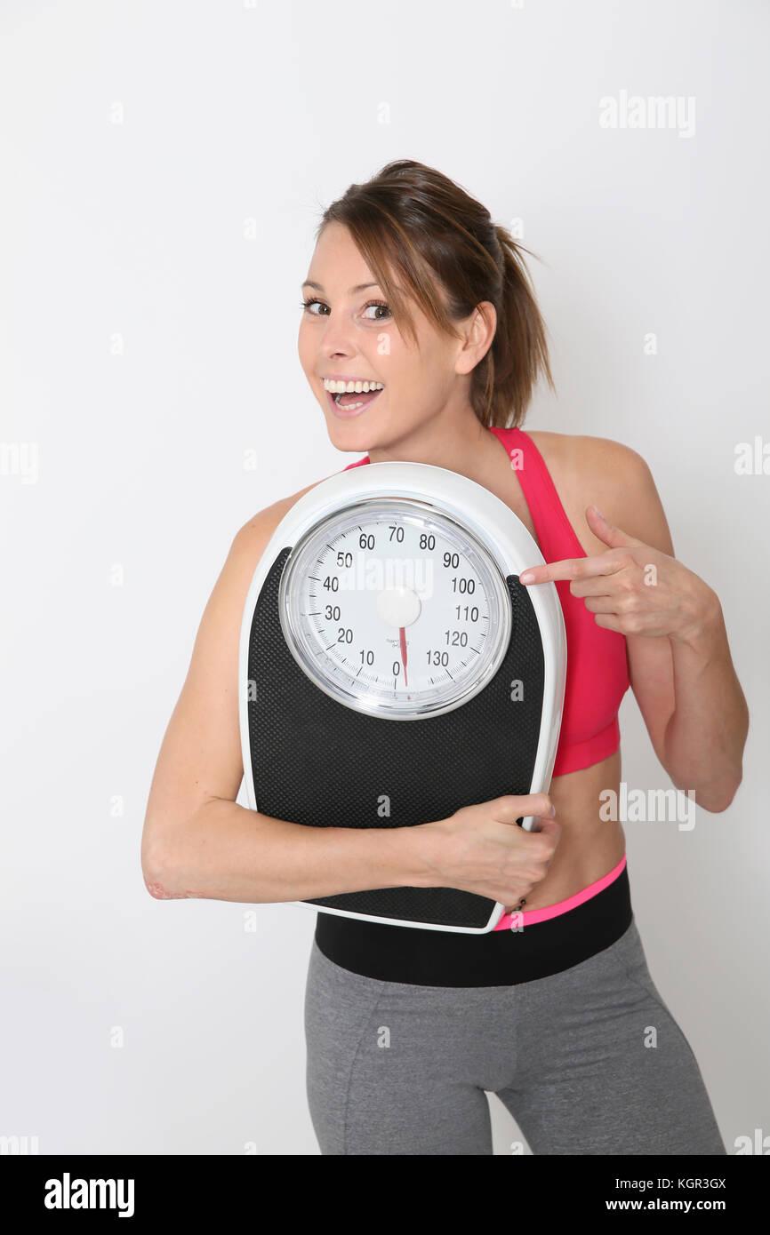 Cheerful girl in fitness'échelle, isolé Photo Stock