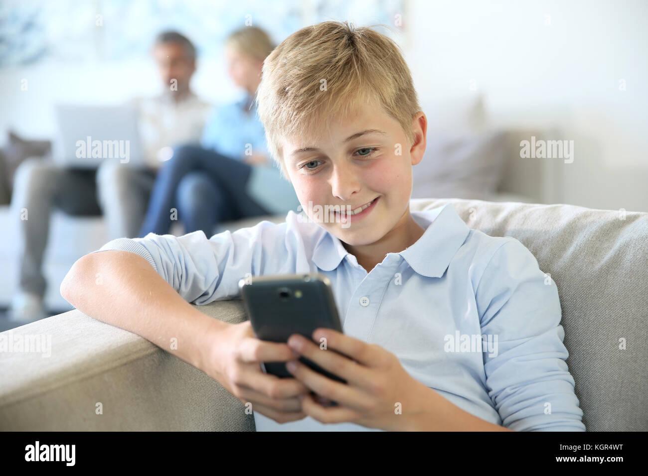 Jouant avec des pré-adolescents, parents smartphone en arrière-plan Photo Stock
