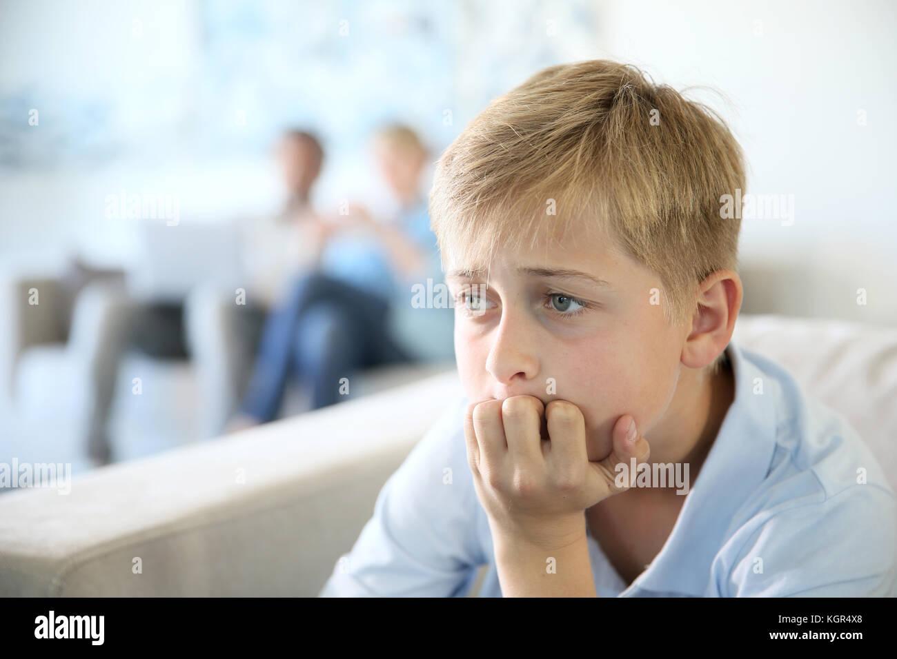 12-year-old boy sitting in table à la maison, les parents en arrière-plan Photo Stock