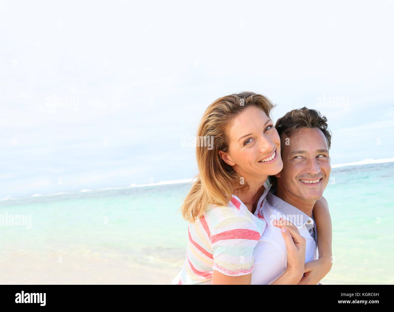 Man giving piggyback ride de petite amie à la plage Photo Stock