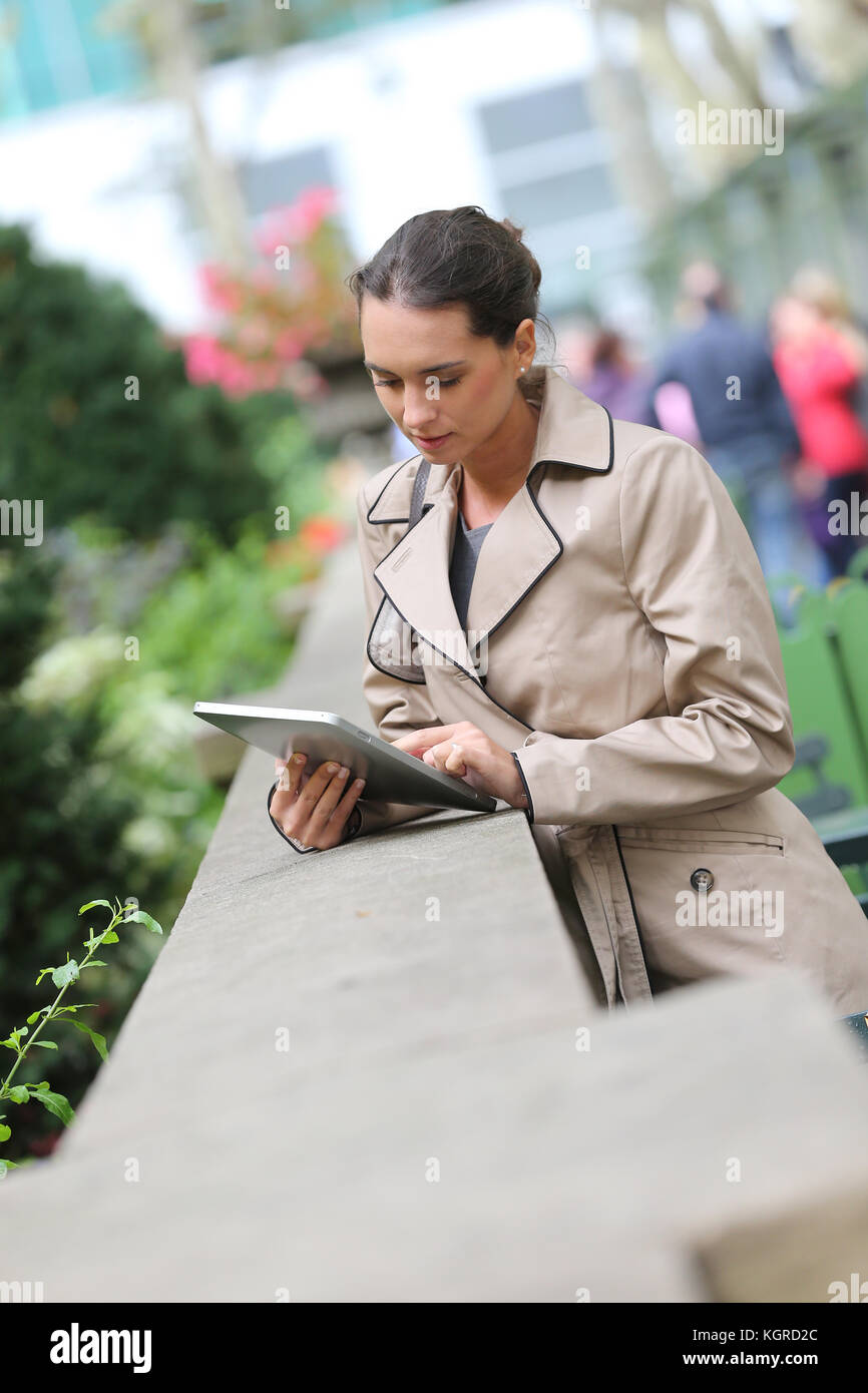 Businesswoman standing in park with digital tablet Photo Stock
