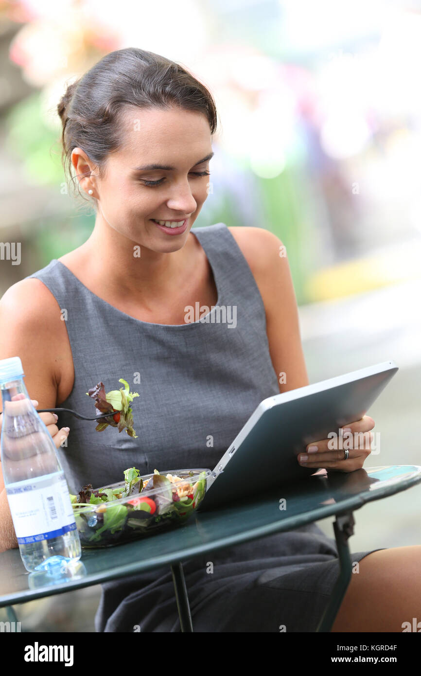 Businesswoman working with tablet tout en déjeunant Photo Stock