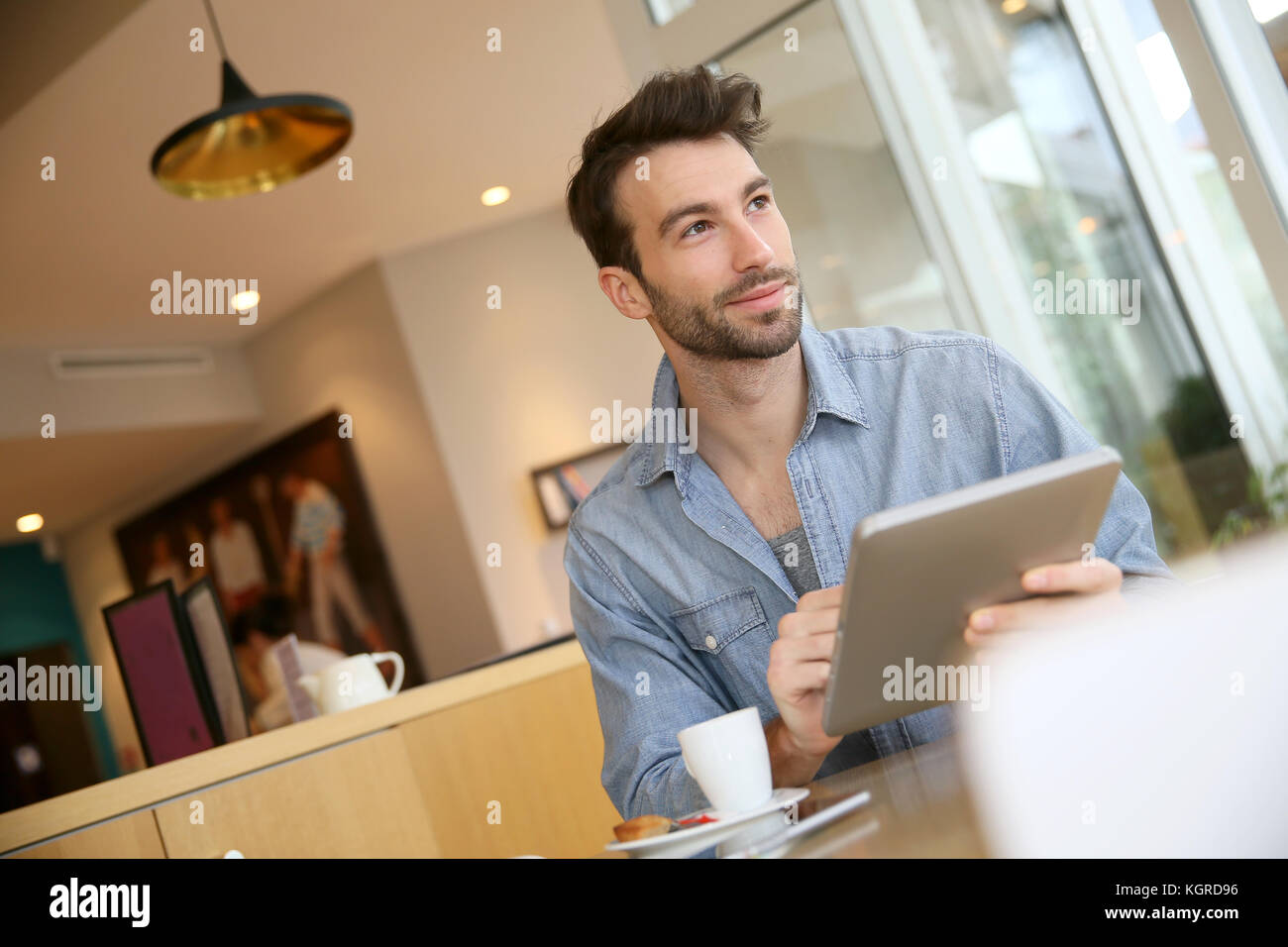 Ferra homme sur digital tablet in coffee shop Photo Stock