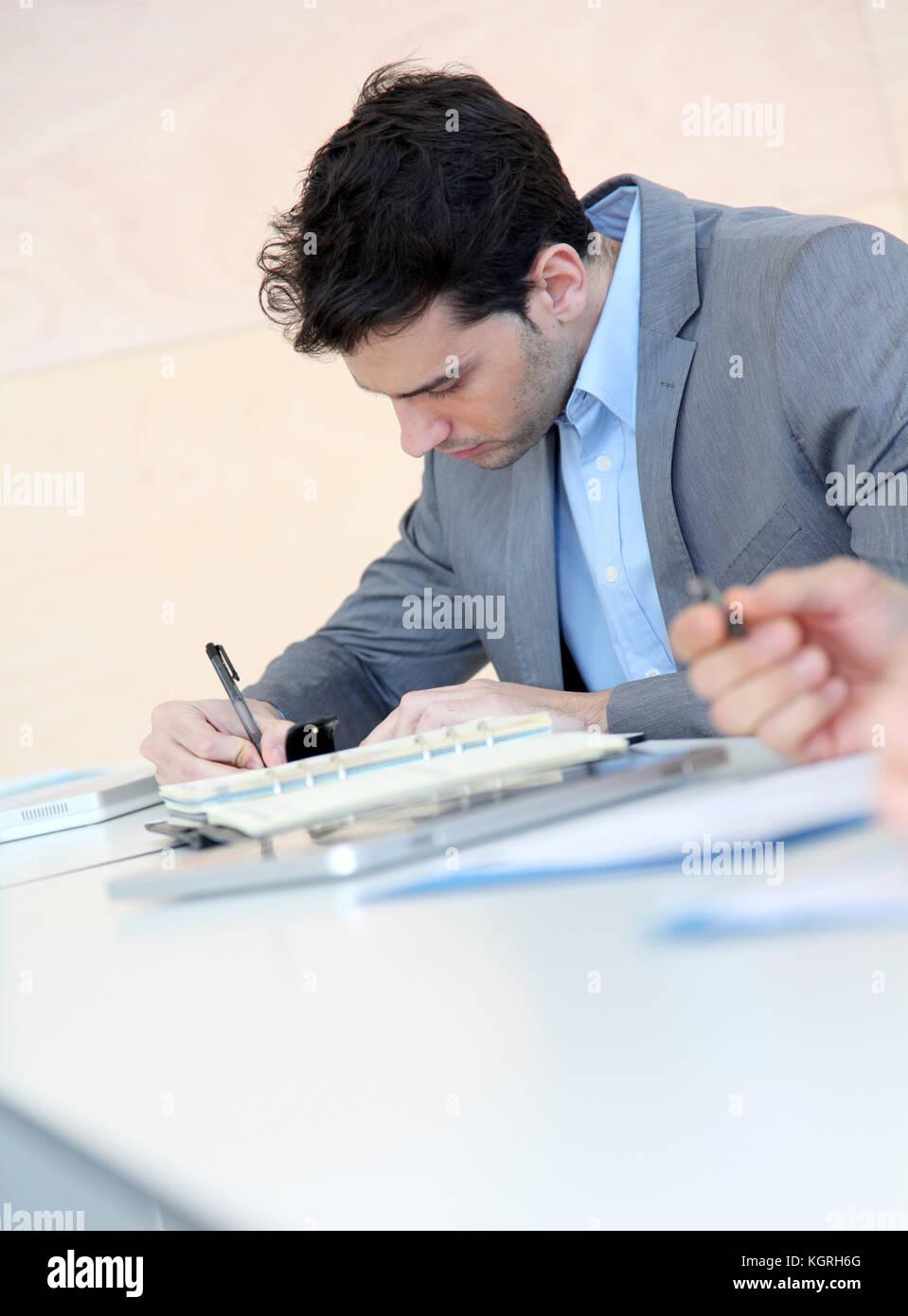 Jeune homme en remplissant le formulaire de demande Photo Stock