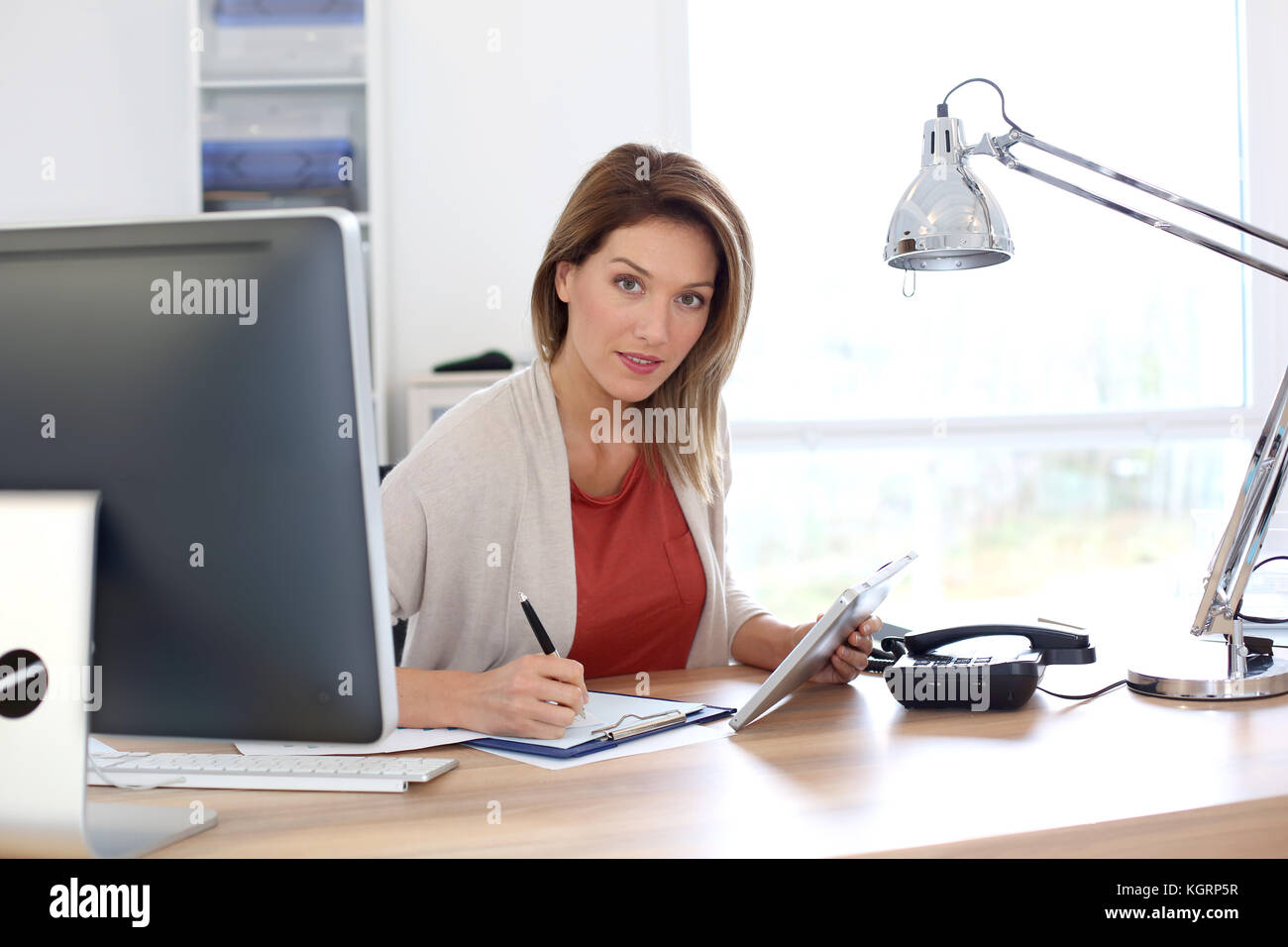 Businesswoman in office travaillant avec tablet Photo Stock