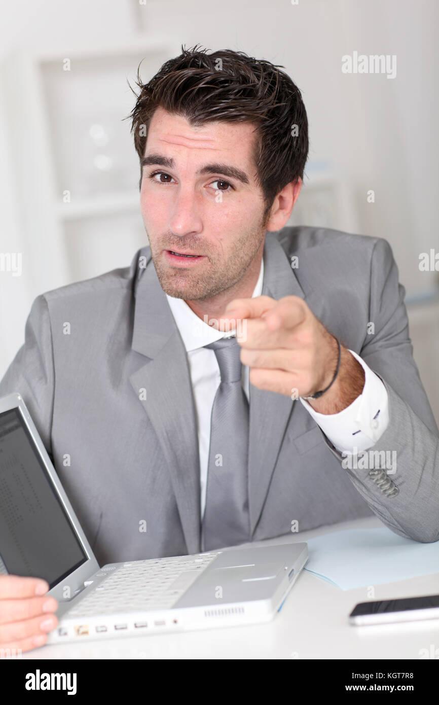 Businessman showing something on laptop computer Photo Stock