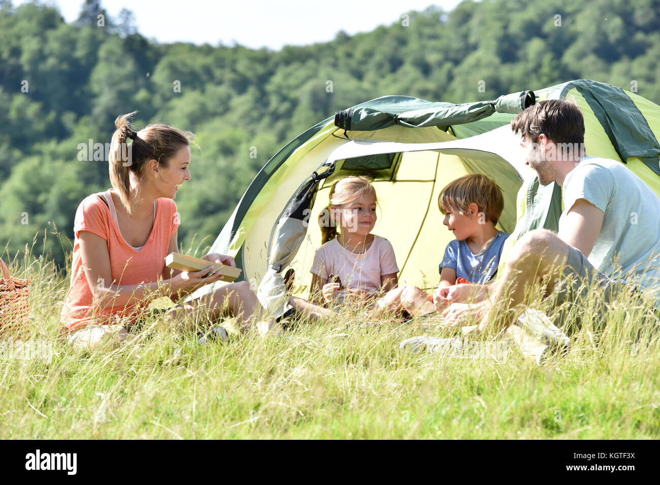 Famille de quatre personnes au camp tente Photo Stock