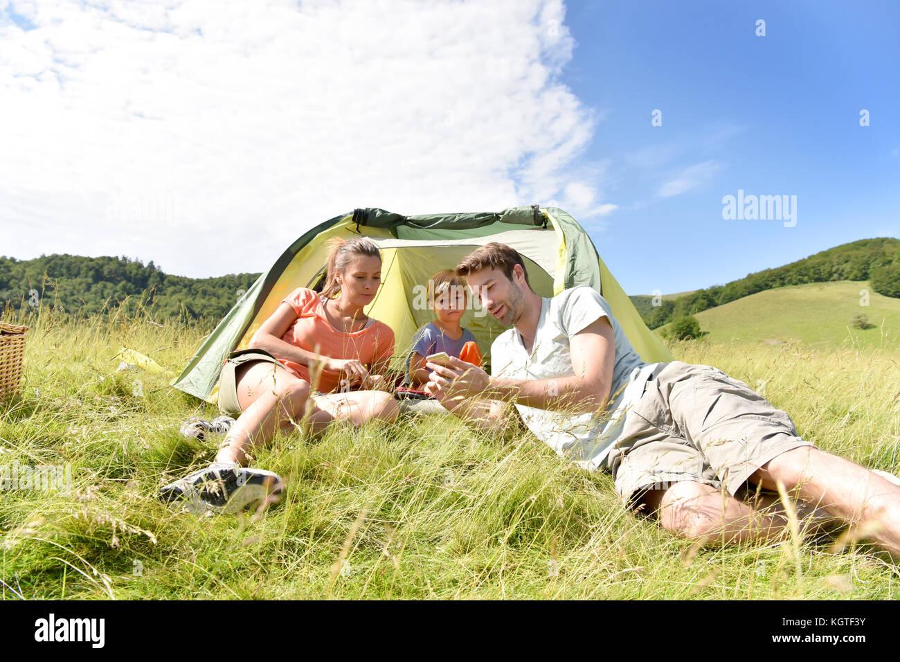 Tente de camping en famille jouer avec smartphone Photo Stock