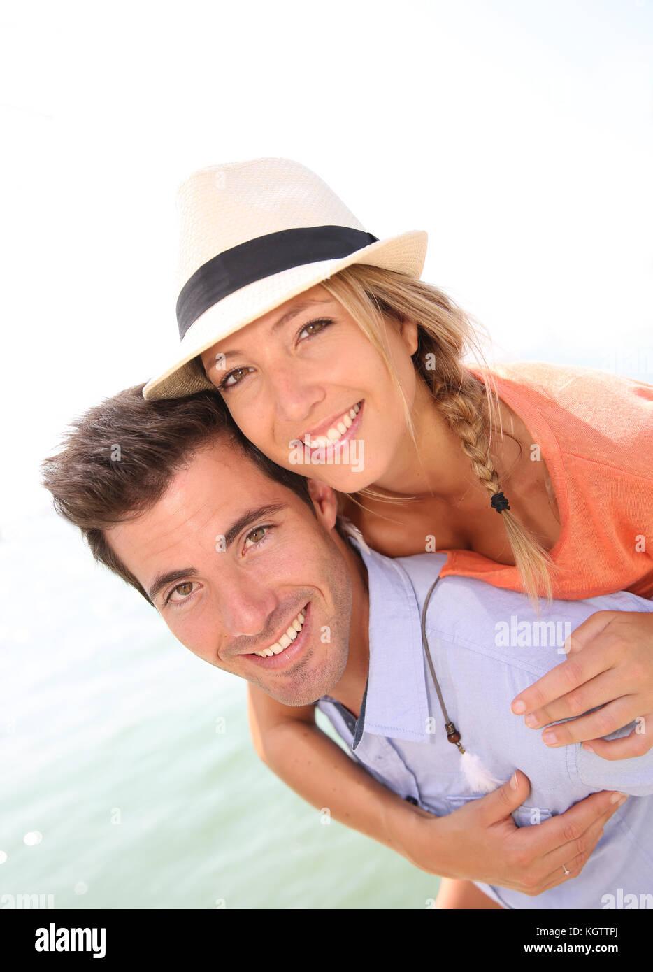 Man giving piggyback ride de belle fille blonde avec chapeau Photo Stock