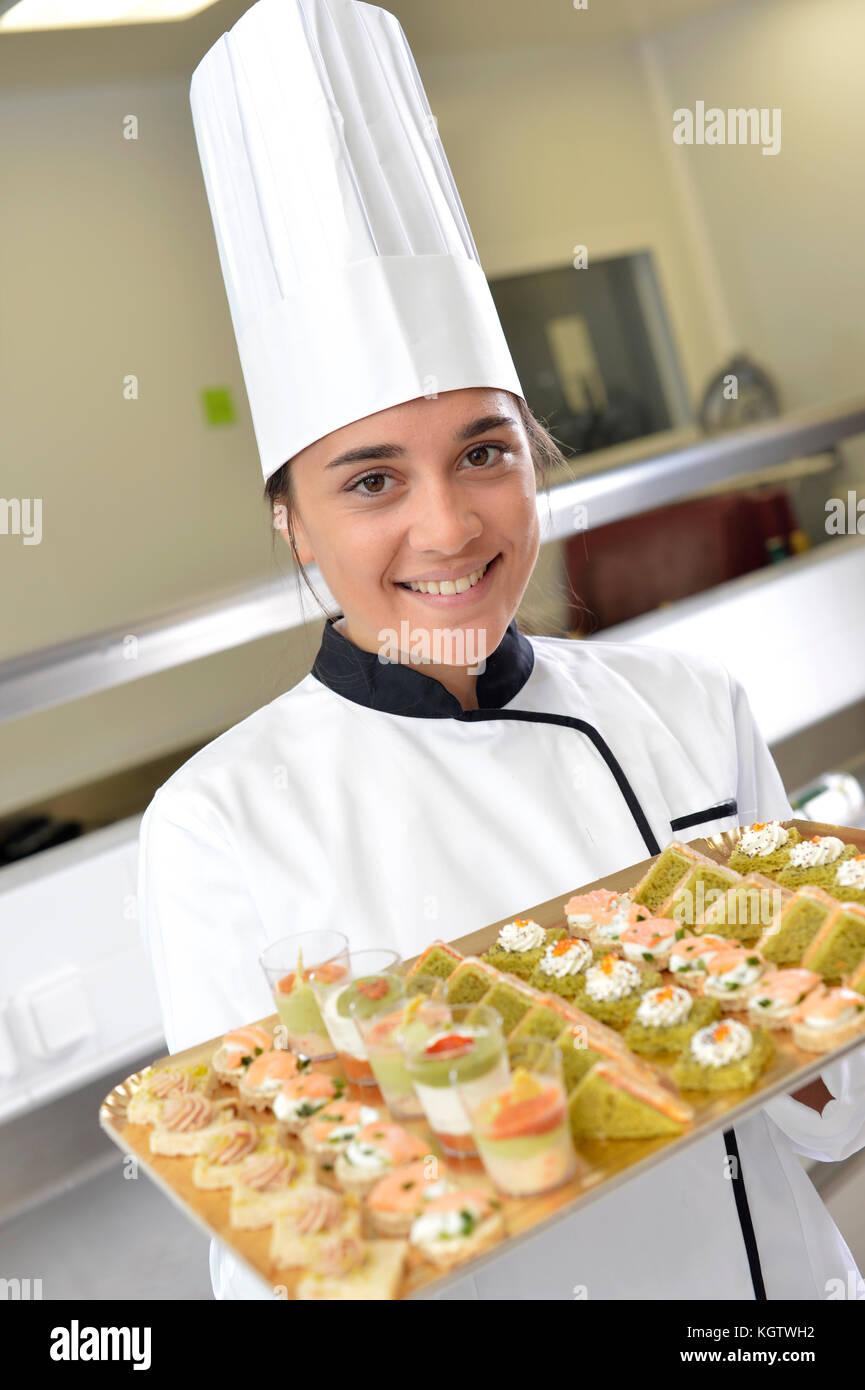 Cheerful young cook plaque de maintien de l'épicerie fine Photo Stock