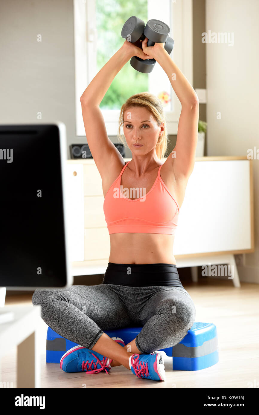 Fille Fitness Photo fitness petite fille levée haltères en face de programme tv banque d