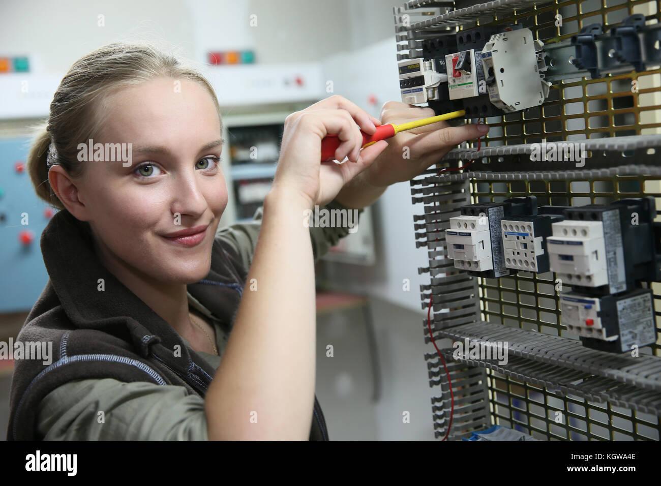 Jeune femme en formation professionnelle mise en place de circuit électrique Photo Stock