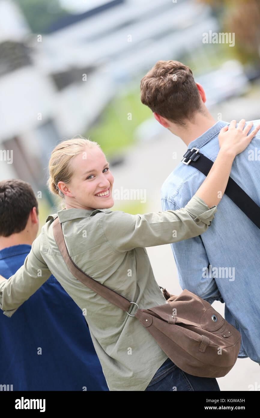 Élève fille qui marche avec des copains Photo Stock