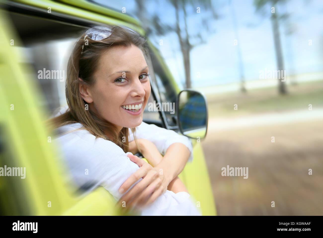 Portrait of smiling woman sitting in vintage camper van Photo Stock