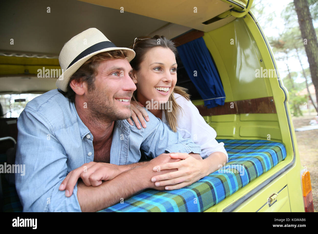 Cheerful young couple portant sur un camping-car Photo Stock