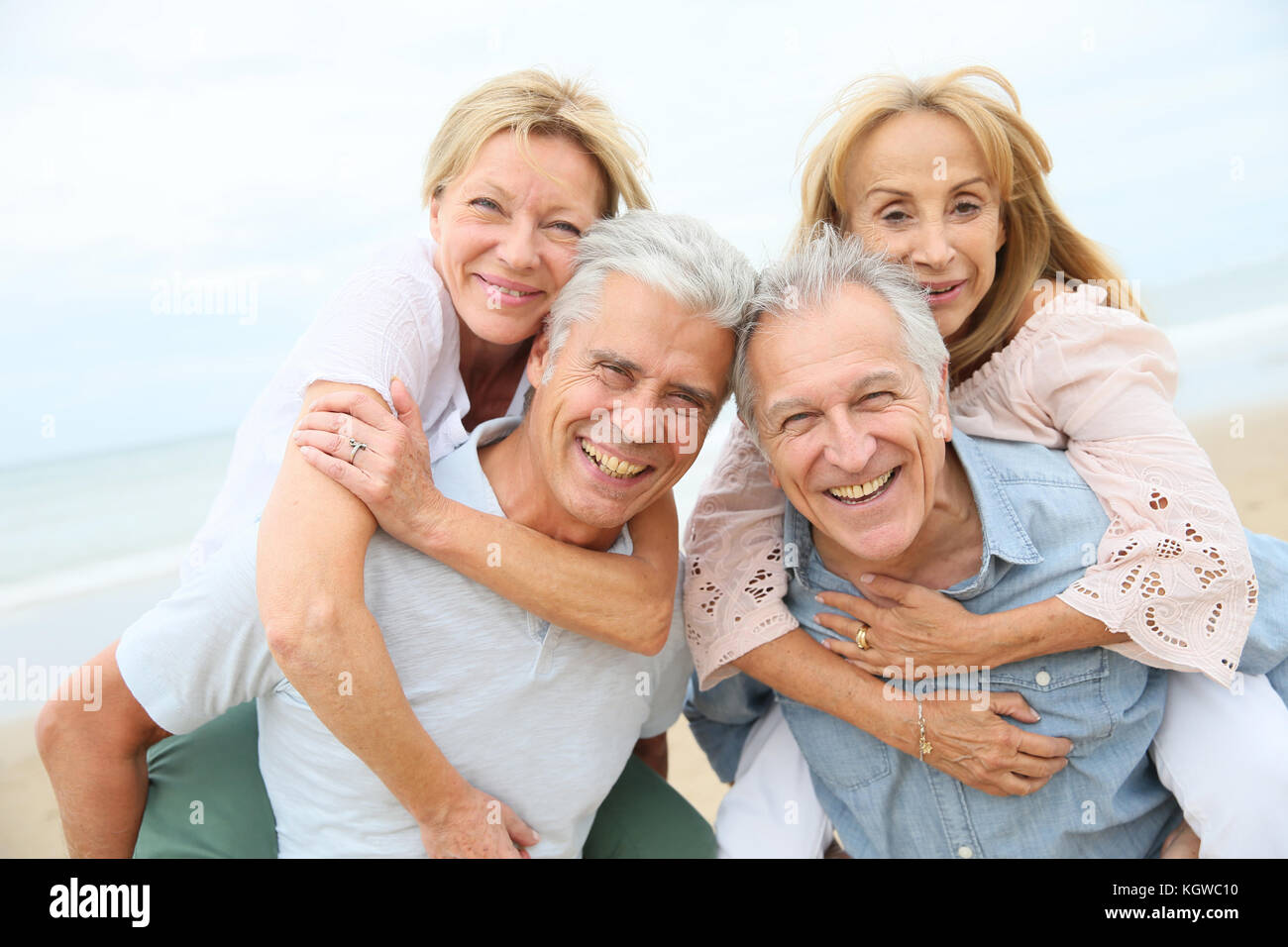 Les hommes aînés donnant piggyback ride pour les femmes âgées Photo Stock