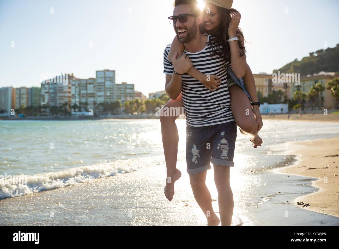 Portrait d'homme heureux de donner sa petite amie un rire Photo Stock