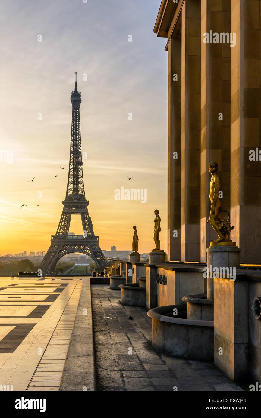 Le soleil levant éclaire l'esplanade du Trocadéro et ses statues en or alors que la Tour Eiffel se Photo Stock