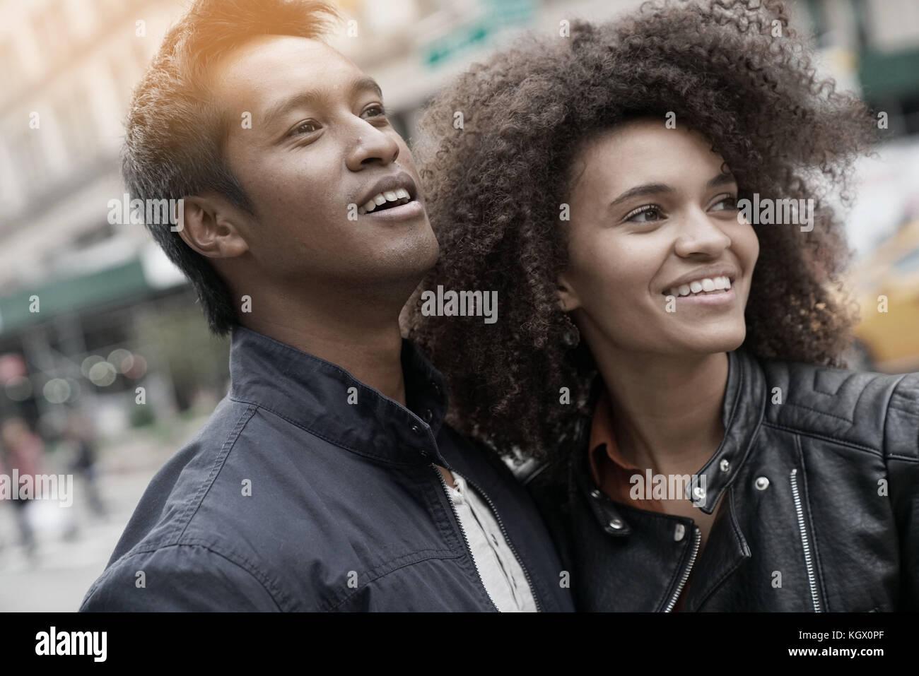 Ethnic couple walking in new york city street sur jour de pluie Photo Stock