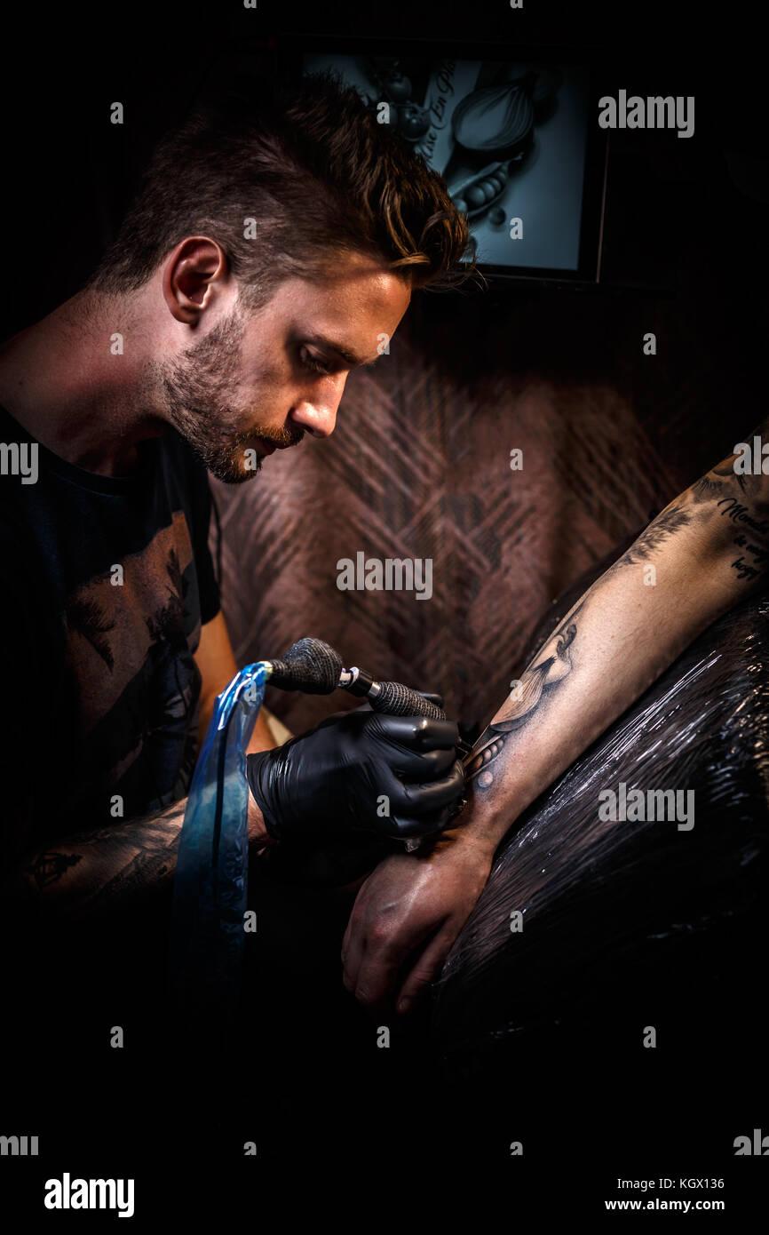 Tatoueur professionnel fait un tatouage sur la main d'un jeune homme Photo Stock